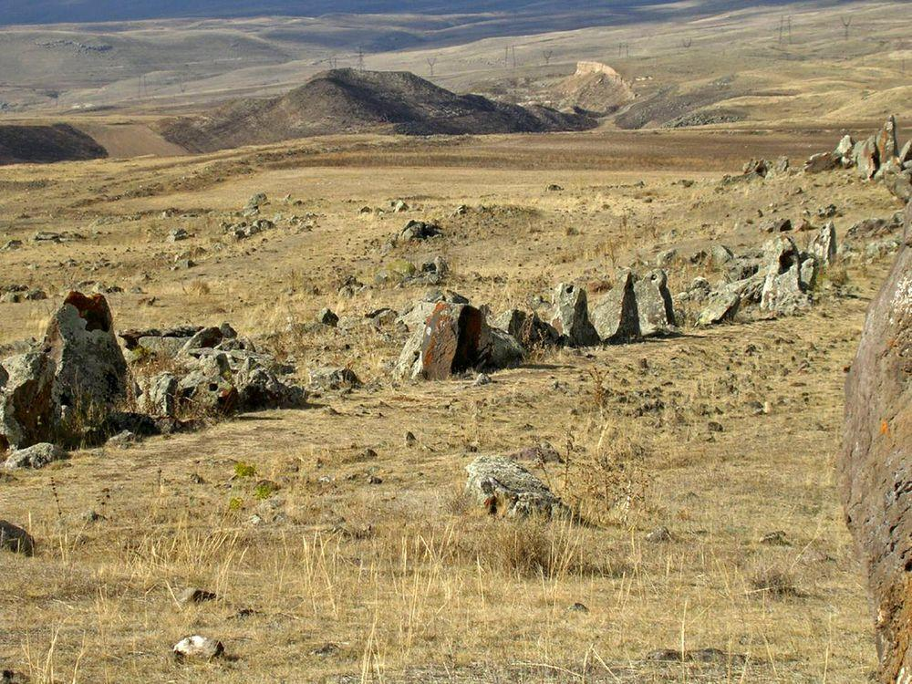 Row of standing stones in Karahunj, holes in some stones are visible, Armenia