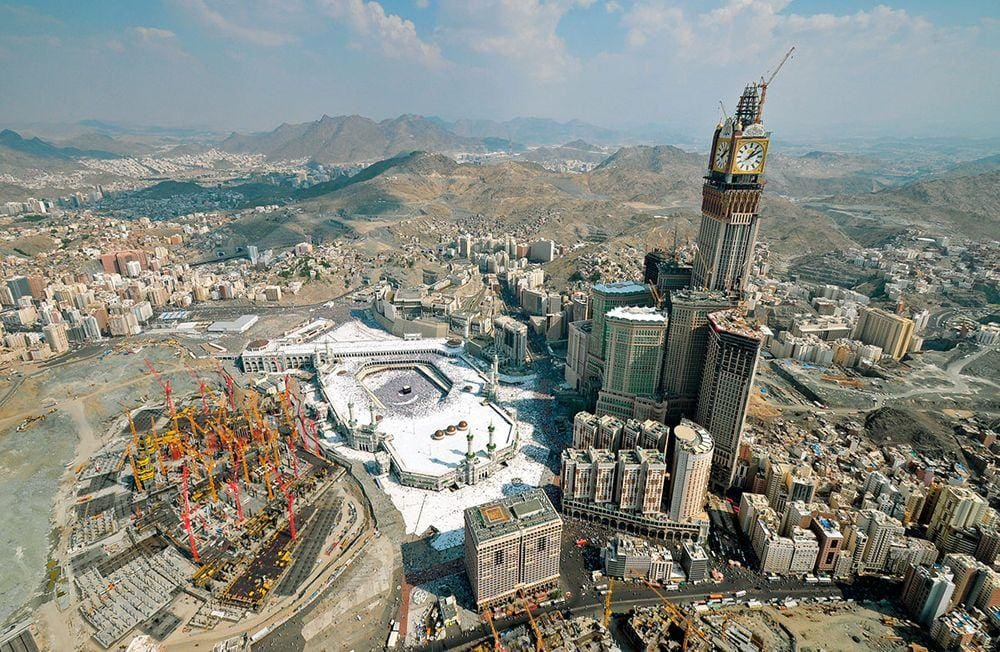 Centre of Mecca from air. White area is Masjid-al-Haram, with the small black cube - Kaaba - in the centre. Abraj Al Bait Towers - world's largest building by floor area and second tallest skyscraper is to the left