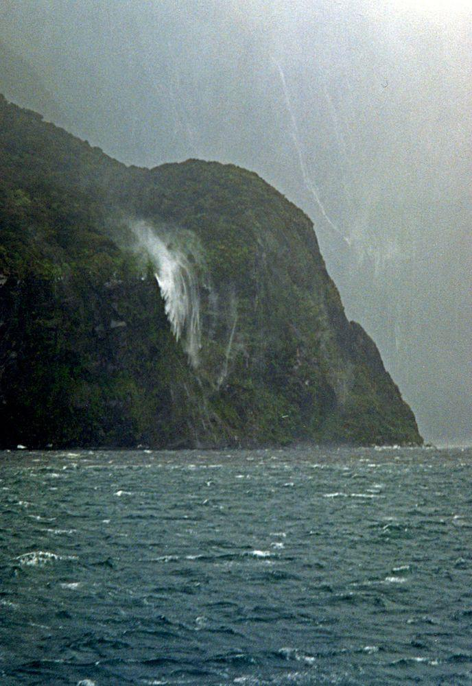 Milford Sound. Waterfall thrown back by a strong gale. Note the much higher falls in the background