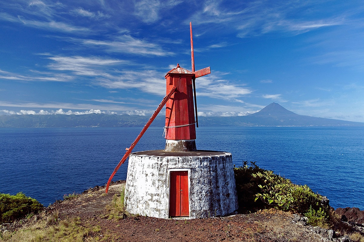 Traditional windmill in São Jorge (Azores) with Mount Pico in the background